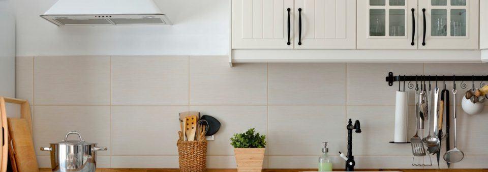 Cozinha com móveis claros e coifa branca