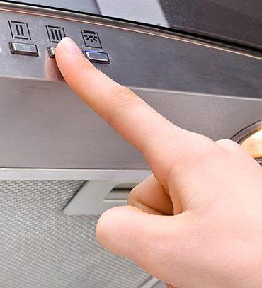 Dedo apertando botão de uma coifa