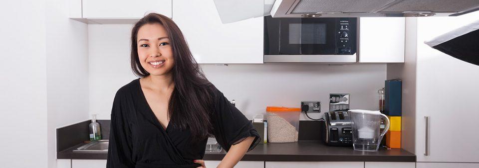 Mulher de preto em uma cozinha branca